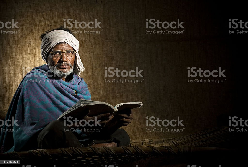 Senior, bespectacled, rural Indian man reading a book royalty-free stock photo