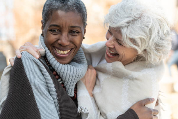 Senior Best friends Two senior friends laugh affectionately together. The women are standing outside on a sunny but cool day. They are dressed in casual sweaters. One woman is of African descent and the other is Caucasian. lgbtqi people stock pictures, royalty-free photos & images