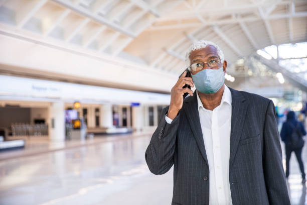 senior black businessman on phone at the airport wearing a mask - businessman covid mask foto e immagini stock