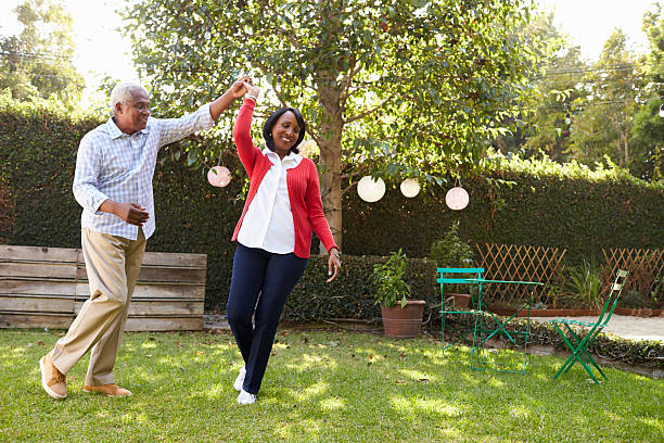 senior black couple dance in their back garden, full length - active lifestyle stock photos and pictures