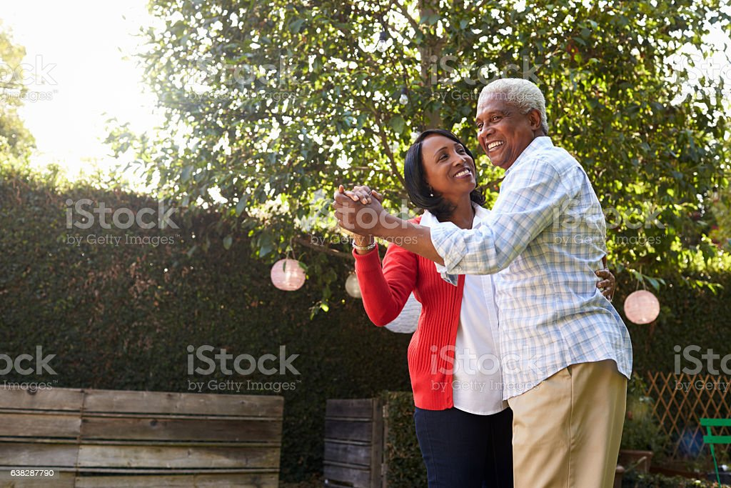 Senior black couple dancing in their back garden stock photo