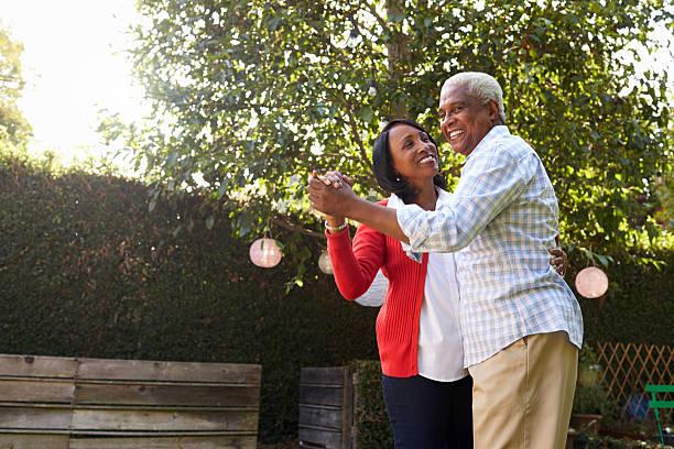 Senior black couple dancing in their back garden stock photo
