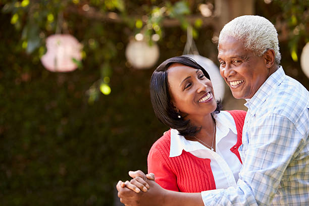 Senior black couple dancing in their backyard, close up stock photo