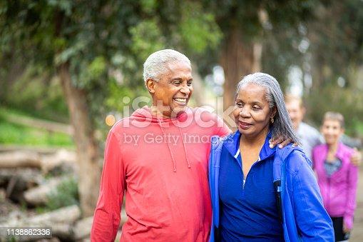 A senior black couple smiles while on a hiking trip