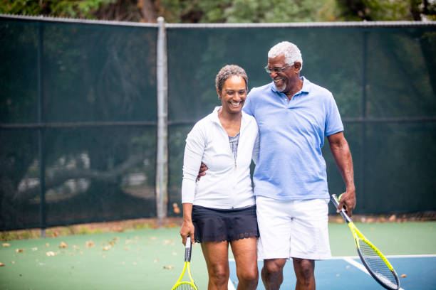 senior black couple on tennis court - baby boomers stock pictures, royalty-free photos & images