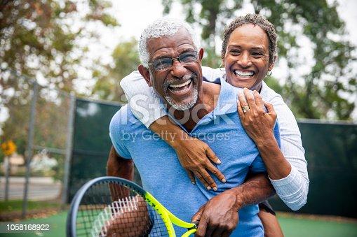 A senior black couple piggyback together on the tennis court.
