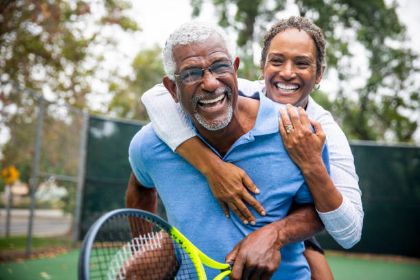 senior black couple on tennis court piggyback - baby boomers stock pictures, royalty-free photos & images