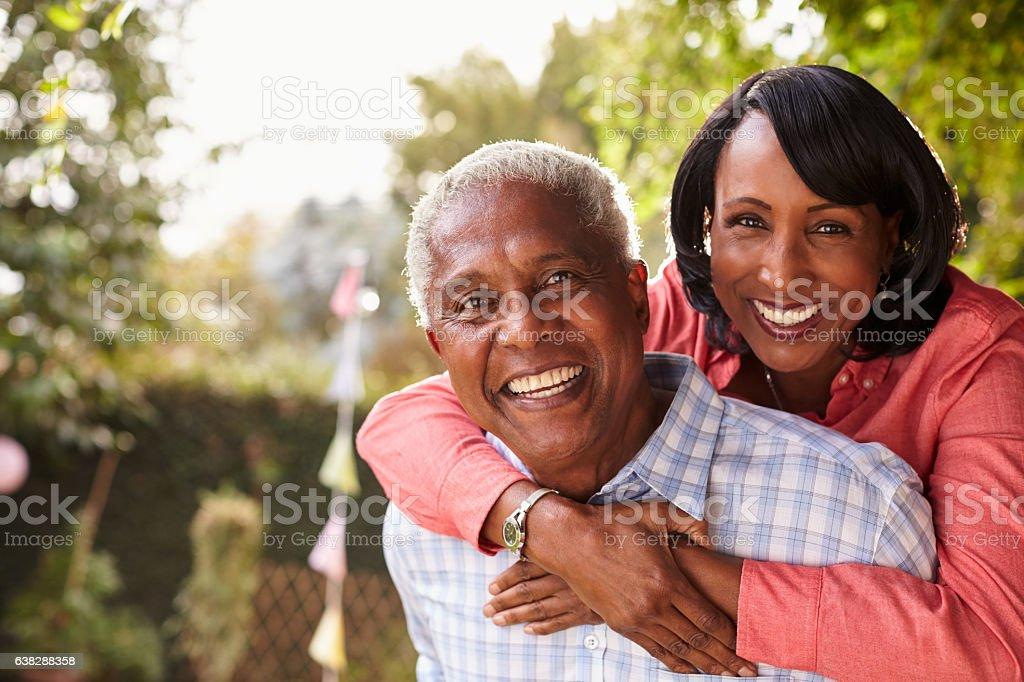Senior black couple piggyback in garden looking at camera stock photo
