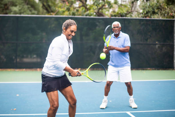senior black couple playing doubles tennis - racket sport stock pictures, royalty-free photos & images