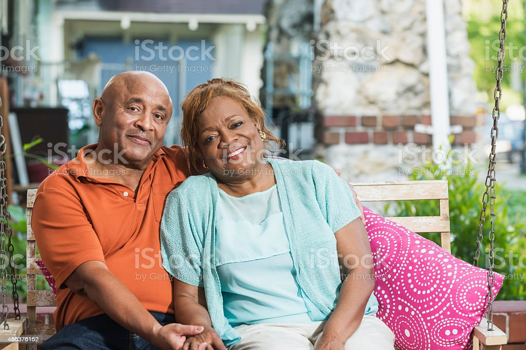 Senior black couple sitting on porch swing holding hands stock photo