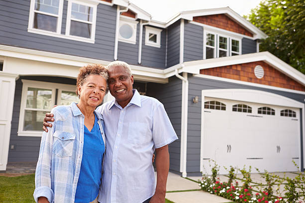 senior black couple standing outside a large suburban house - senior housing stock photos and pictures