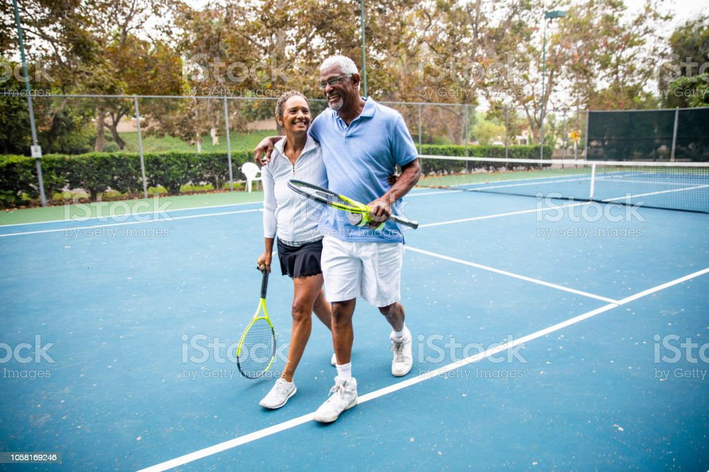 Senior Black Couple Walking Off the Tennis Court stock photo