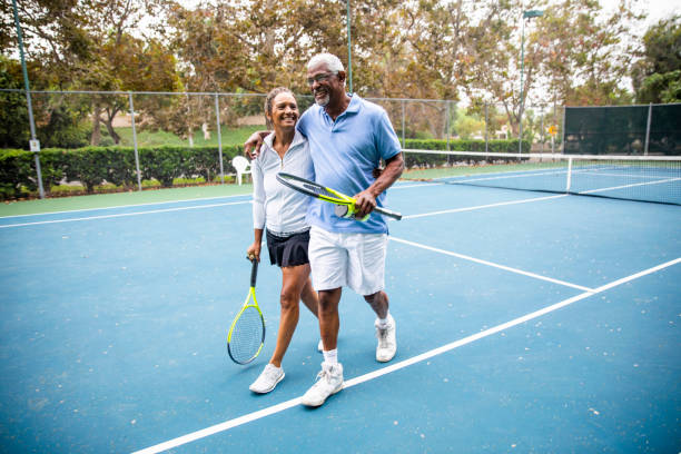 senior black couple walking off the tennis court - tennis stock pictures, royalty-free photos & images
