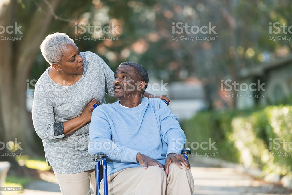 Senior black couple with man in wheelchair stock photo