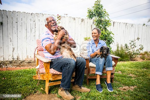 A senior black couple playing outdoors with their two dachshunds