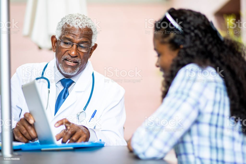 A senior black doctor meets with a young black woman
