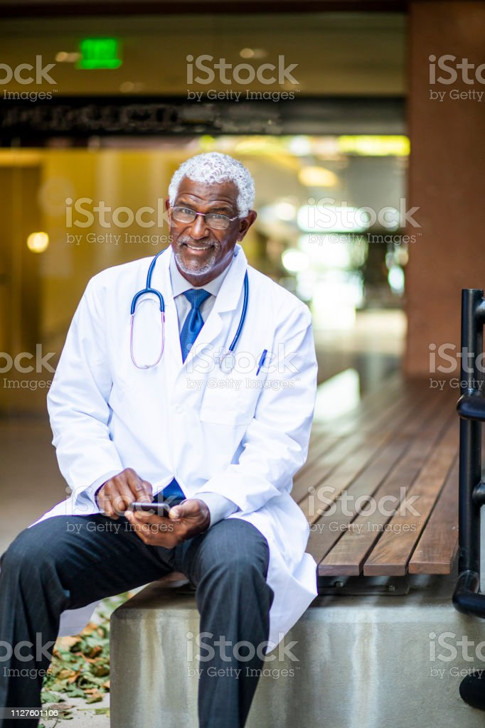 A senior black doctor texting while looking at the camera