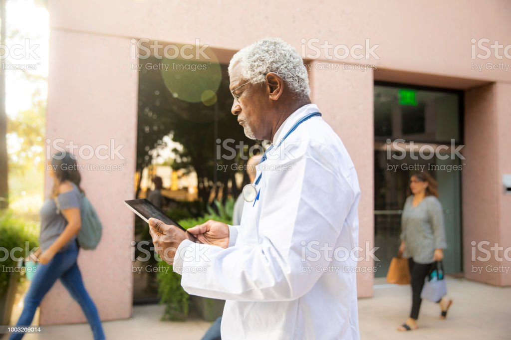 A senior black doctor using a tablet while walking