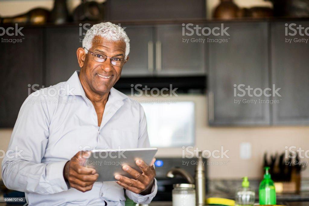 Senior noir homme navigation sur tablette à la maison - Photo