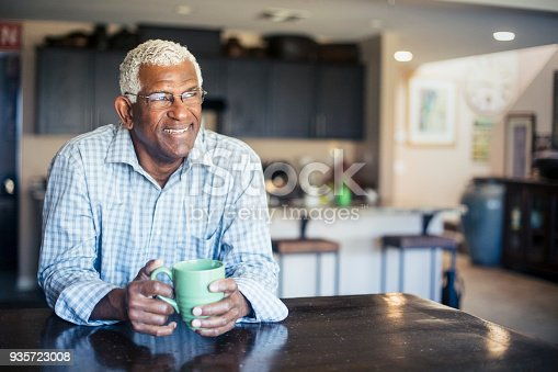 A senior black man enjoys a cup of coffee at home