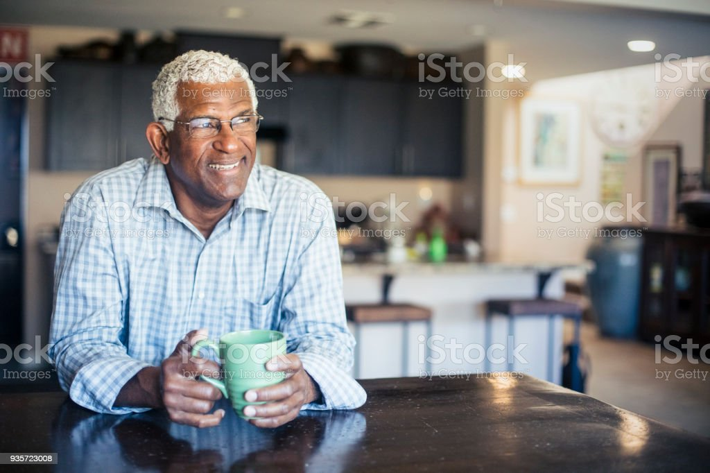Senior Black Man Enjoying a Cup of Coffee at Home stock photo