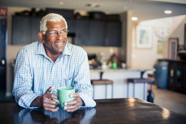 senior schwarzer mann bei einer tasse kaffee zu hause - senior mann porträts stock-fotos und bilder