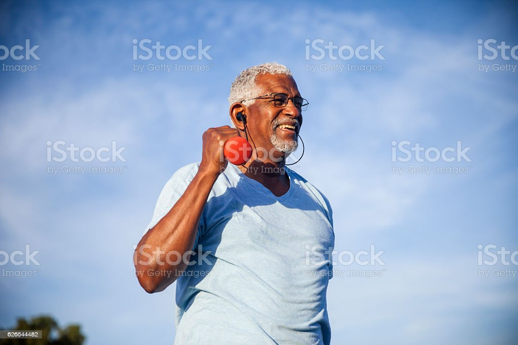 Senior Black Man Exercising Outdoors with Dumbells stock photo