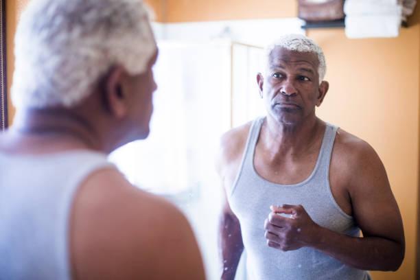 senior schwarzer mann immer bereit im badezimmer - alte spiegel stock-fotos und bilder