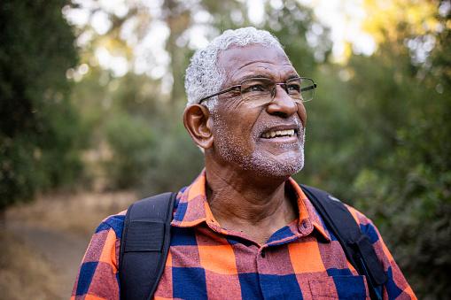 A senior black man with white hair hiking outdoors.