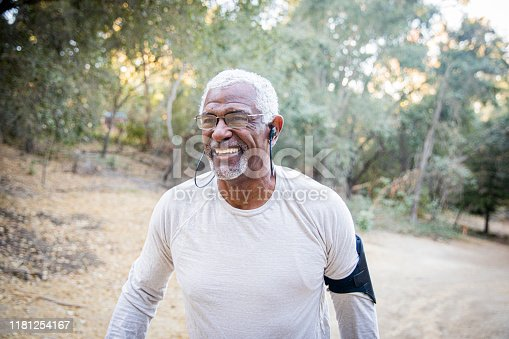 A senior black man with headphones during a workout