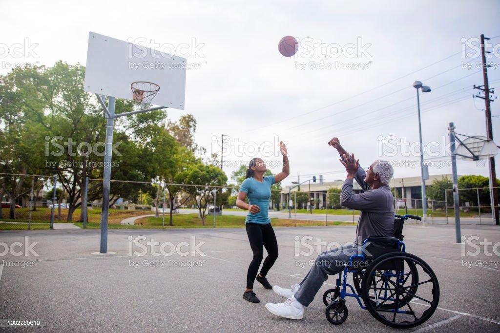 Senior hombre de negro en silla de ruedas tiro baloncesto - foto de stock
