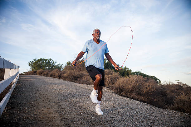 senior black man jumping rope outdoors - springseil stock-fotos und bilder
