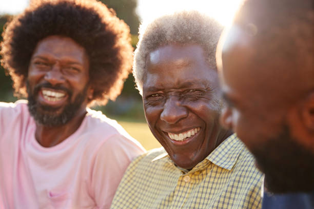 senior black man laughing with his two adult sons, close up - older brother imagens e fotografias de stock