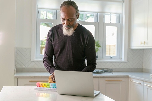 A healthy senior black man stands at the counter in his kitchen. He just completed a video call medical consultation with his doctor or pharmacist and his laptop computer is open on the counter. The man is sorting medication and placing appropriate doses in a daily pill box organizer.