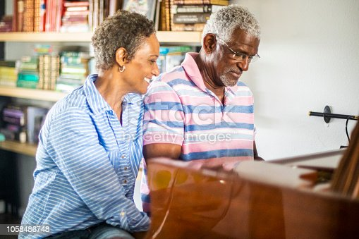 A senior black couple playing the piano with his wife listening and watching