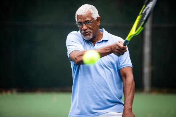 senior black man playing tennis - racket sport stock pictures, royalty-free photos & images