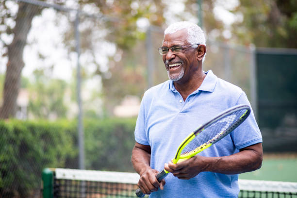 Senior Black Man Playing Tennis Portrait of a senior black man with a tennis racket active seniors stock pictures, royalty-free photos & images