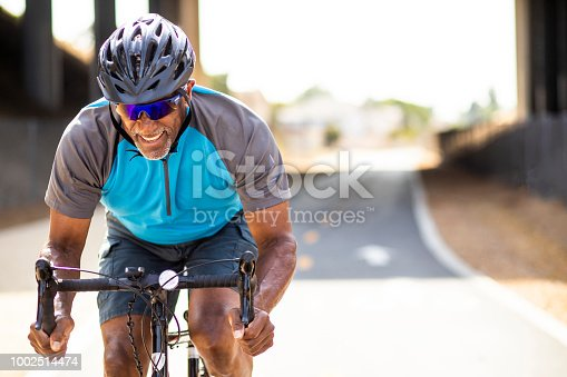 A senior black man sprints on his road bike training for a race.