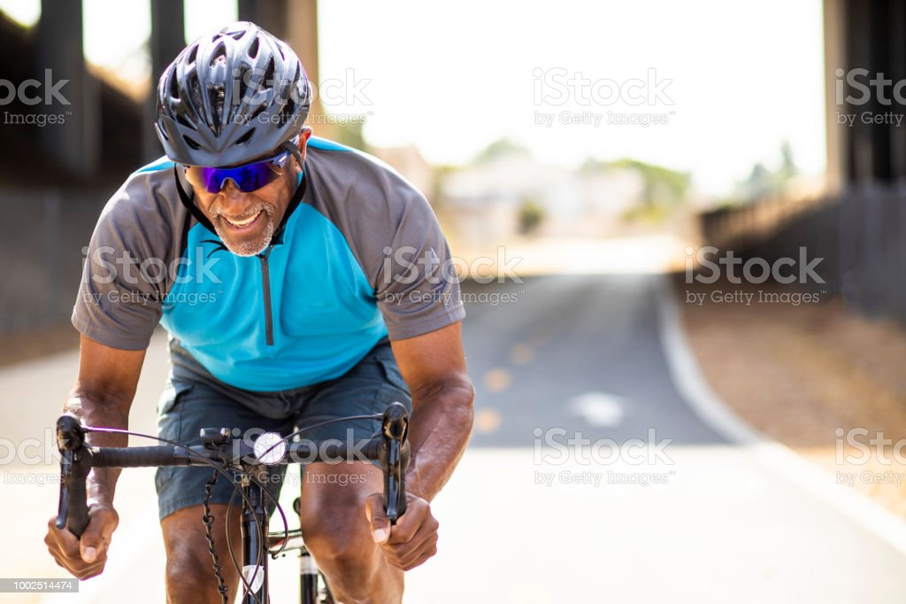 Senior Black Man Racing on a Road Bike stock photo