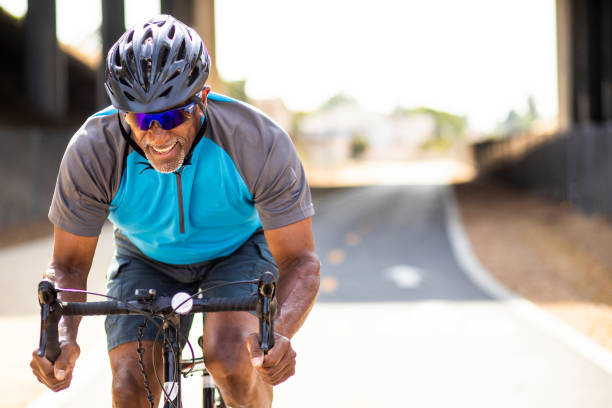 senior black man racing on a road bike - cycling stock photos and pictures