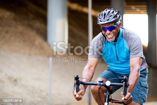 A senior black man rides a road bike on a trail for exercise.