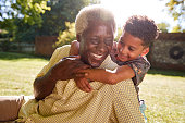 Senior black man sitting on grass, embraced by his grandson