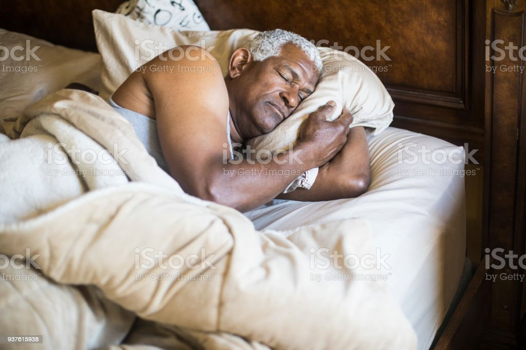 Senior Black Man Sleeping and Waking Up stock photo