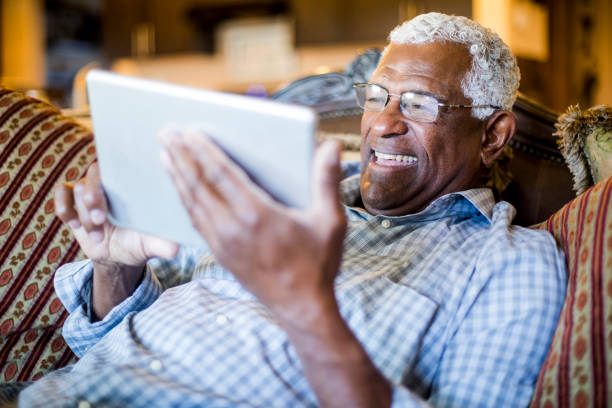 Senior Black Man Streaming on Tablet stock photo