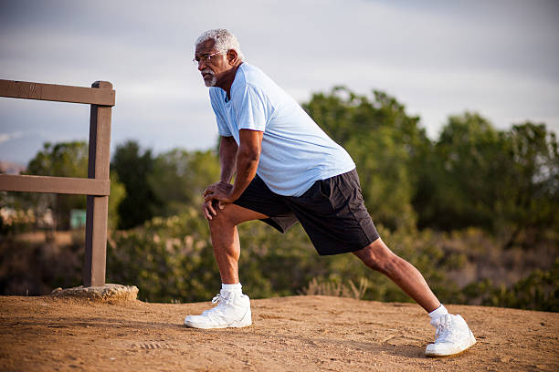 Senior Black Man Stretching and Exercising Outdoors An attractive senior black man exercises outdoors with various muscle stretches hamstring stock pictures, royalty-free photos & images