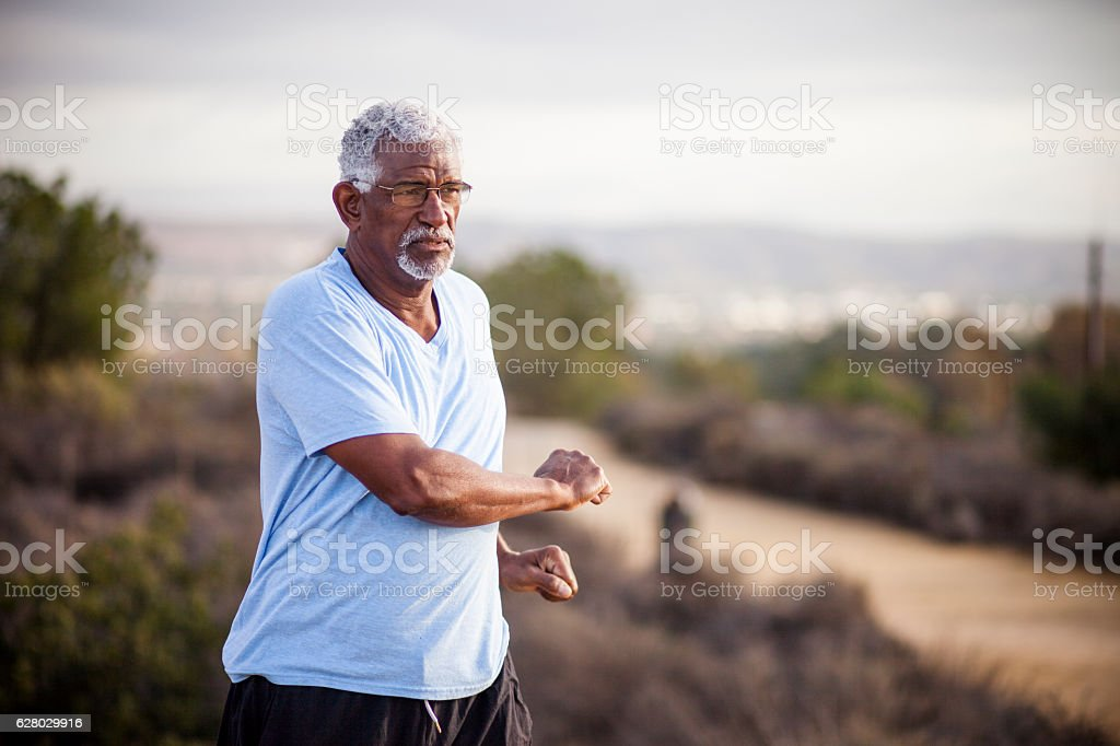 Senior Black Man Stretching and Exercising Outdoors stock photo