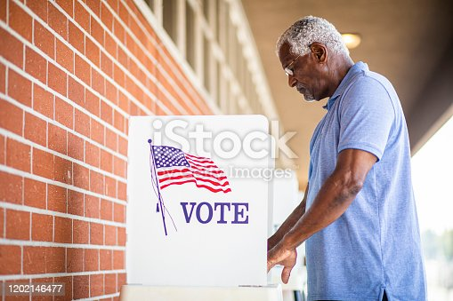 1001757174 istock photo Senior Black Man Voting at Booth 1202146477