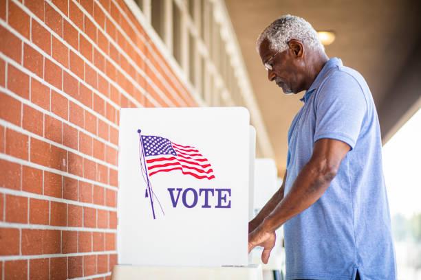 senior black man voting at booth - выборы президента стоковые фото и изображения