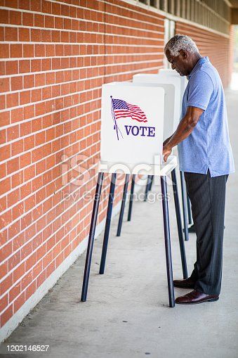 1001757174 istock photo Senior Black Man Voting at Booth 1202146527