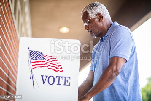 1001757174 istock photo Senior Black Man Voting at Booth 1202146689